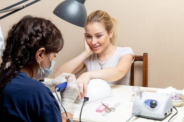 Vista frontal jovem mulher consertando as unhas pela manicure dentro do quarto beleza manicure unhas cuidados com as mãos