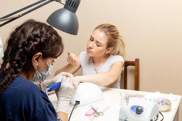 Vista frontal jovem mulher consertando as unhas pela manicure dentro do quarto beleza mulher manicure unha senhora autocuidada