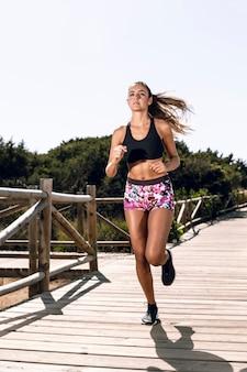 Vista frontal jovem mulher correndo