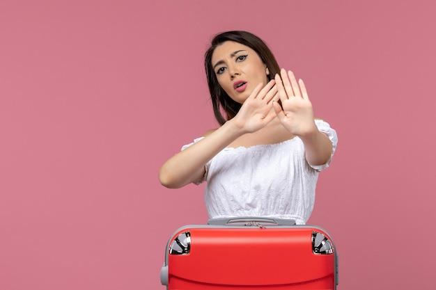 Vista frontal jovem mulher de férias com sua bolsa em fundo rosa no exterior