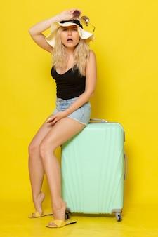 Vista frontal jovem mulher de férias sentada em sua bolsa verde na parede amarela cores garota feminina viagem viagem mar