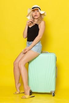 Vista frontal jovem mulher de férias sentada em sua bolsa verde na parede amarela garota feminina viagem viagem mar