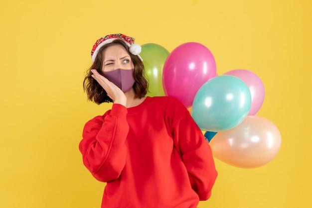 Vista frontal jovem mulher escondendo balões em cor de máscara estéril férias emoção ano novo natal