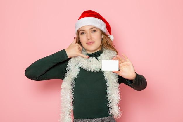 Vista frontal jovem mulher segurando um cartão de banco branco sorrindo na parede rosa cor emoção modelo férias natal ano novo