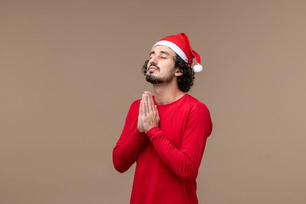 Vista frontal jovem orando em fundo marrom, férias de emoções de natal