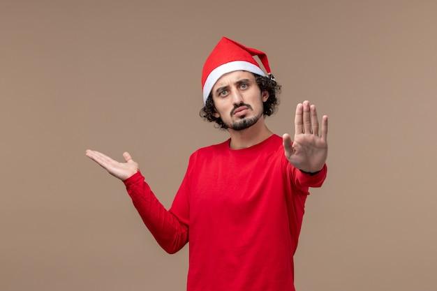 Vista frontal jovem pedindo para parar em um fundo marrom nas emoções do feriado natal