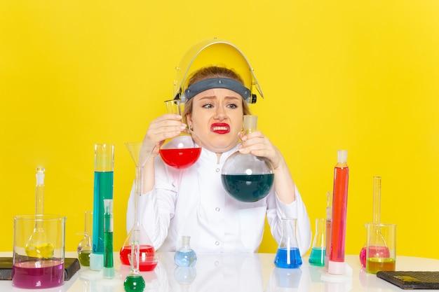 Vista frontal, jovem química feminina em terno branco sentada e segurando diferentes soluções no trabalho de química do espaço amarelo