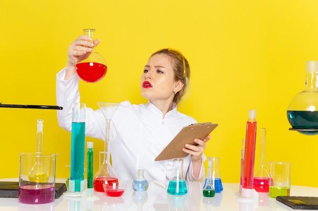 Vista frontal, jovem química feminina em um terno branco com soluções de ed, trabalhando com eles e sentada no espaço amarelo.