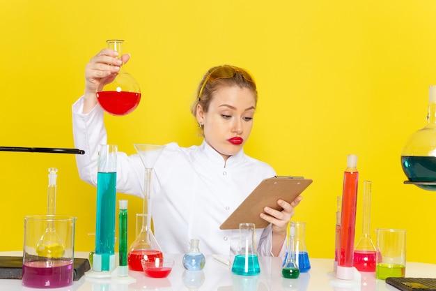 Vista frontal, jovem química feminina em um terno branco com soluções de ed, trabalhando com eles e sentada no trabalho de processo de química espacial amarela