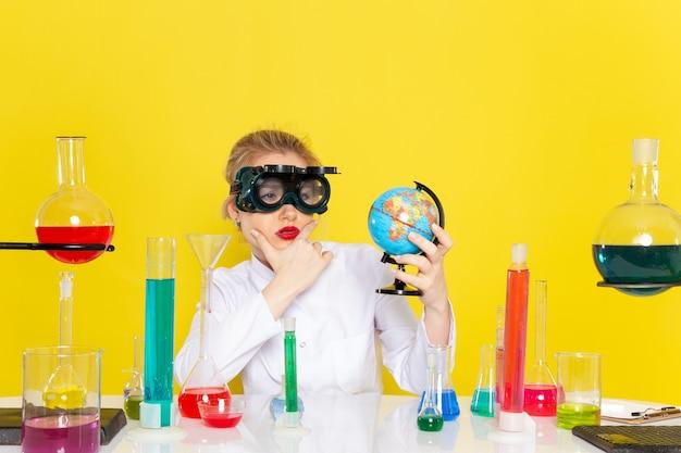 Vista frontal, jovem química feminina em um terno branco com soluções de ed, verificando o globo com a máscara no espaço amarelo.