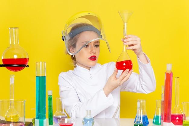 Vista frontal, jovem química feminina em um terno branco com soluções educacionais trabalhando com eles usando um capacete nos testes de química do espaço amarelo