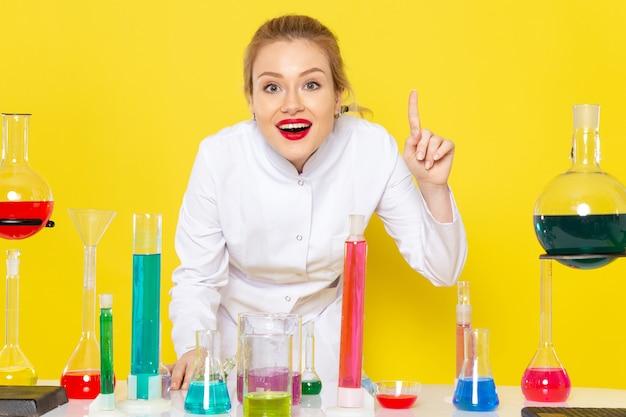 Vista frontal, jovem química feminina em um terno branco em frente à mesa com soluções de ed, sorrindo no experimento de química do espaço amarelo