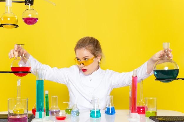 Vista frontal, jovem química feminina em um terno branco em frente à mesa com soluções de educação e trabalho, misturando-se com a ciência da química espacial amarela