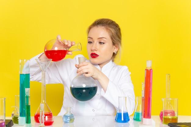 Vista frontal, jovem química feminina em um terno branco segurando diferentes soluções, misturadas no trabalho de química do espaço amarelo
