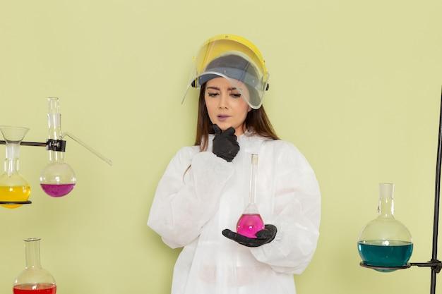 Vista frontal, jovem químico feminino em traje de proteção especial, segurando uma solução rosa e pensando no trabalho de química de parede verde feminino ciência laboratório