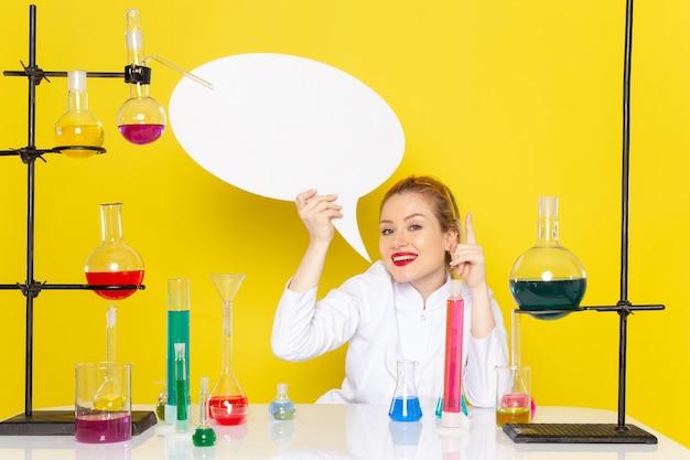 Vista frontal, jovem químico feminino sentado em um terno branco com diferentes soluções, segurando uma placa branca e sorrindo no trabalho de processo de ciência química espacial amarelo