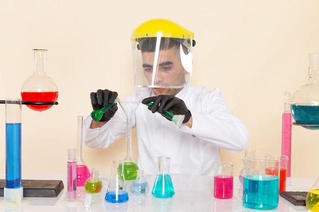 Vista frontal, jovem químico masculino em um terno especial branco na frente da mesa com soluções coloridas trabalhando com eles na mesa creme.