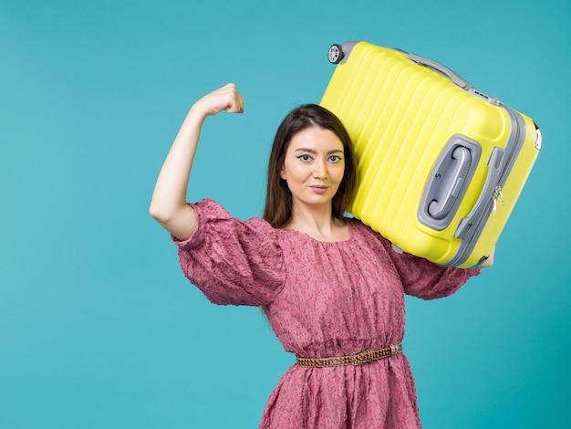 Vista frontal jovem saindo de férias com sua bolsa amarela em fundo azul verão viagem humana mulher mar