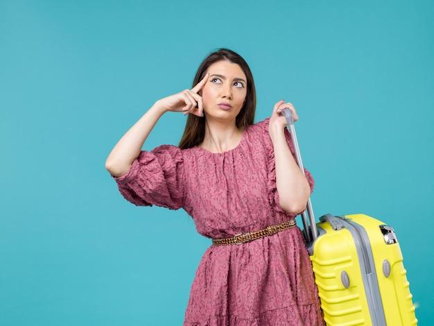 Vista frontal jovem saindo de férias com sua bolsa amarela em fundo azul viagem verão mulher humana viagem mar