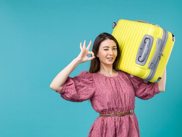 Vista frontal jovem saindo de férias com sua bolsa amarela na mesa azul viagem de verão viagem humana mulher mar