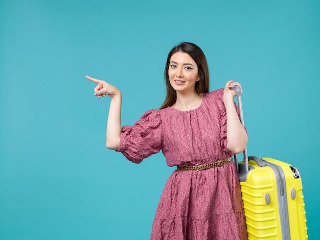 Vista frontal jovem saindo de férias com sua bolsa amarela no fundo azul verão mulher viagem viagem humana mar