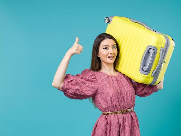 Vista frontal jovem saindo de férias com sua bolsa amarela no fundo azul viagem de verão viagem humana mulher mar