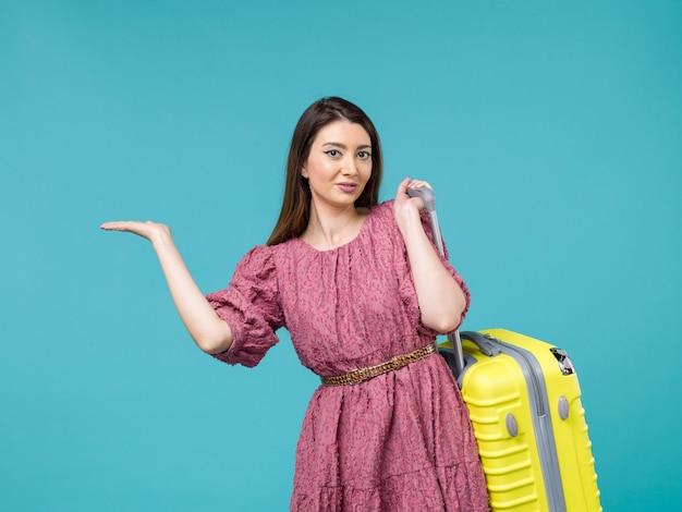 Vista frontal jovem saindo de férias com sua bolsa amarela no fundo azul viagem verão viagem mulher mar humano