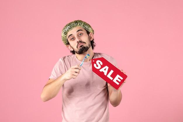 Vista frontal jovem segurando a escova de dentes e a placa de identificação de venda no fundo rosa