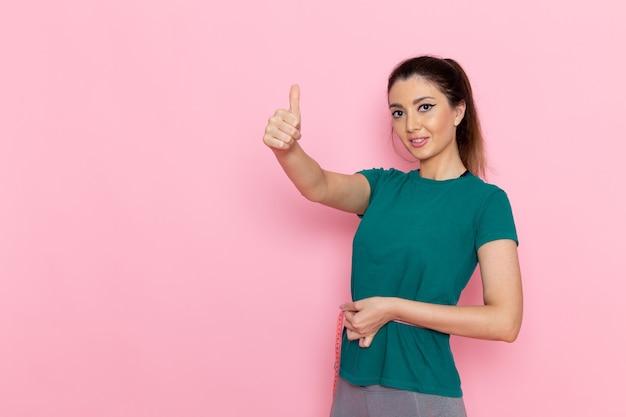 Vista frontal jovem segurando a medida da cintura na parede rosa beleza esporte exercício atleta workouts slim