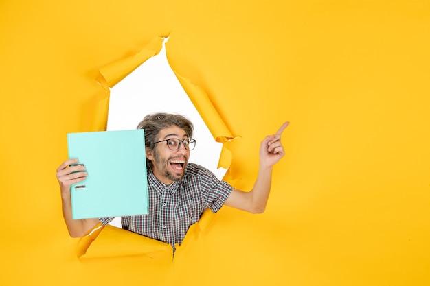 Vista frontal jovem segurando arquivo verde sobre fundo amarelo cor trabalho ano novo escritório emoção trabalho férias