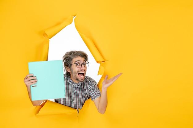 Vista frontal jovem segurando arquivo verde sobre fundo amarelo cor trabalho ano novo natal emoção trabalho feriado