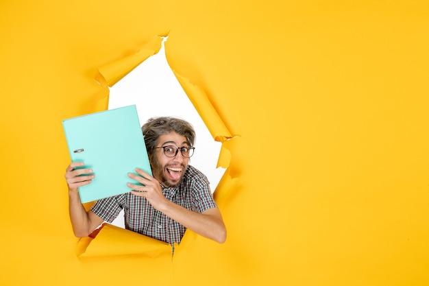 Vista frontal jovem segurando arquivo verde sobre fundo amarelo cor trabalho emoção férias natal trabalho