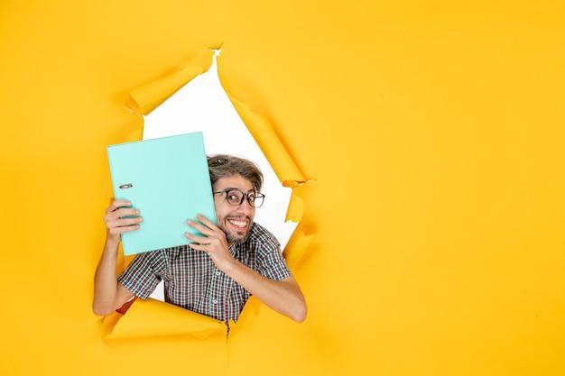 Vista frontal jovem segurando arquivo verde sobre fundo amarelo cor trabalho escritório emoção feriado natal trabalho