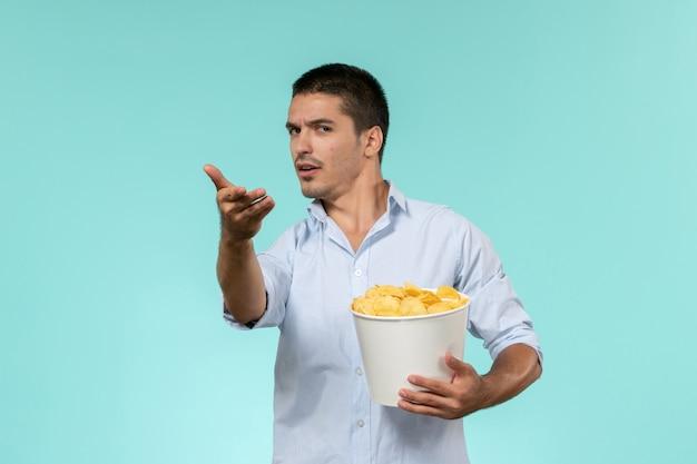 Vista frontal jovem segurando batatas cips na parede azul solitário filmes remotos cinema