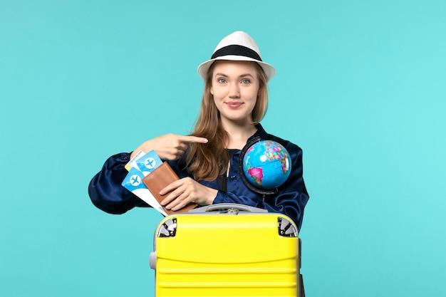 Vista frontal jovem segurando bilhetes e um globo no fundo azul avião viagem mulher mar viagem de férias