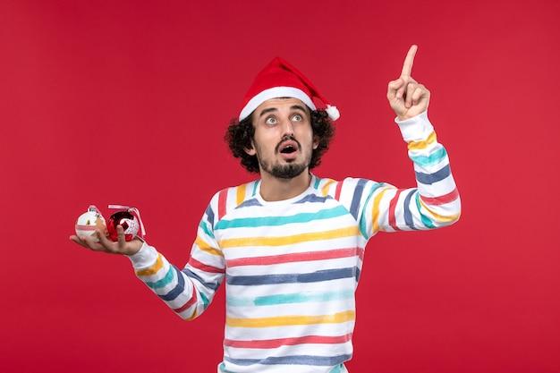 Vista frontal jovem segurando brinquedos da árvore de natal na parede vermelha, ano novo, vermelho, humanos, feriado
