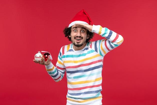 Vista frontal jovem segurando brinquedos da árvore de natal na parede vermelha feriado ano novo vermelho