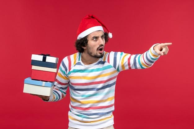 Vista frontal jovem segurando feriado apresenta na parede vermelha emoção de ano novo vermelho
