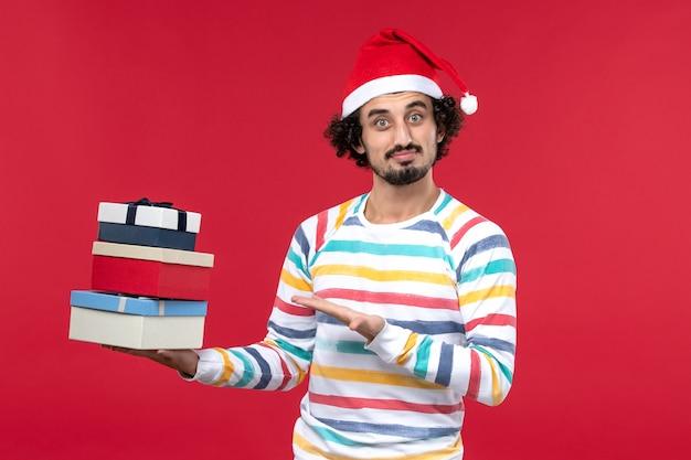 Vista frontal jovem segurando feriado apresenta na parede vermelha emoção de feriado de ano novo