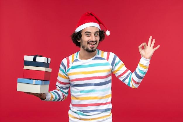 Vista frontal jovem segurando feriado apresenta na parede vermelha emoção de feriados de ano novo