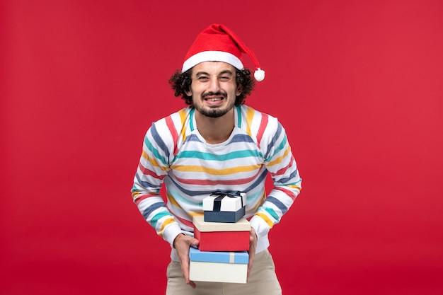 Vista frontal jovem segurando feriado presente na parede vermelha feriado ano novo emoção