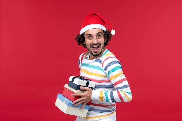 Vista frontal jovem segurando feriado presente na parede vermelha feriados ano novo emoção