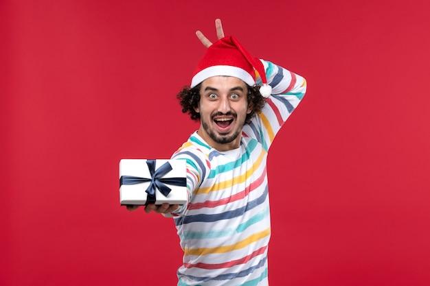 Vista frontal jovem segurando feriado presente na parede vermelha feriados de ano novo vermelho emoção