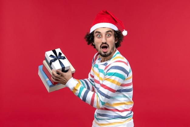 Vista frontal jovem segurando feriado presentes na parede vermelha feriados ano novo emoção
