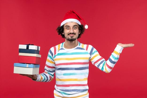 Vista frontal jovem segurando o feriado apresenta no feriado de emoção de ano novo de parede vermelha