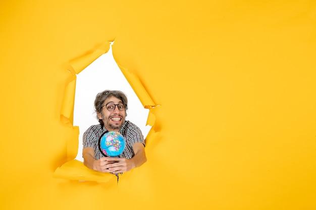Vista frontal jovem segurando o globo terrestre no fundo amarelo mundo feriado emoção natal país planeta
