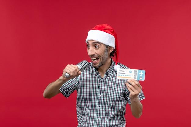 Vista frontal jovem segurando o ingresso com o microfone no piso vermelho, música festiva, emoção