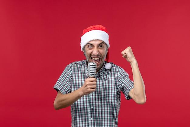 Vista frontal jovem segurando o microfone na parede vermelha emoção feriado cantor música