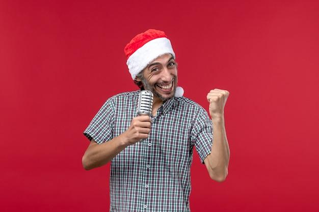 Vista frontal jovem segurando o microfone na parede vermelha, emoção, feriado, música, cantor