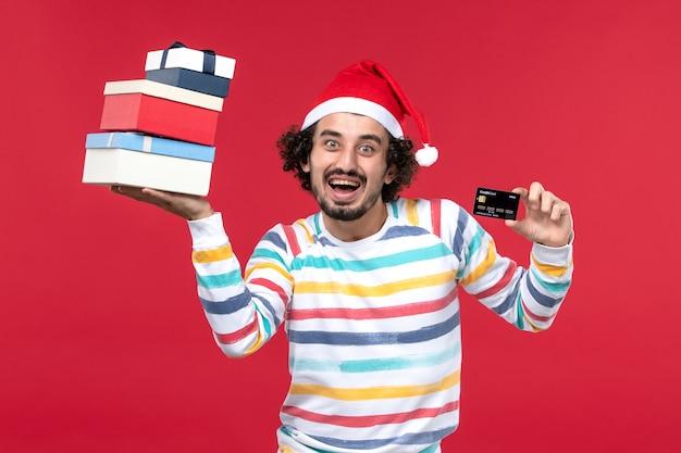Vista frontal jovem segurando presentes e cartão do banco na parede vermelha ano novo dinheiro vermelho emoção